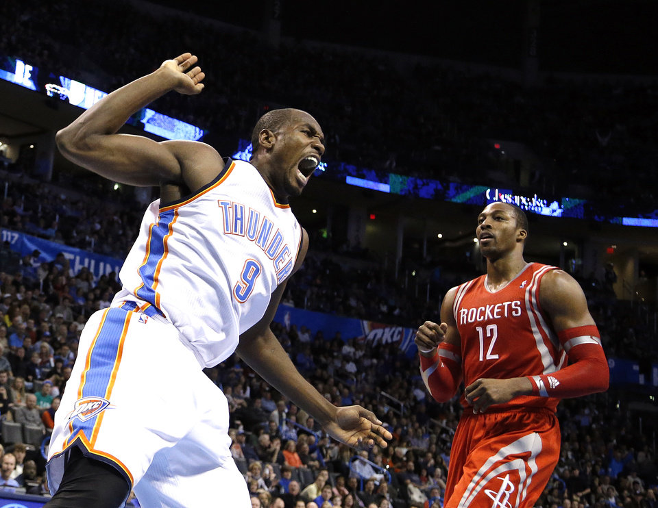 Oklahoma City 's Serge Ibaka (9) celebrates his dunk in front of Houston's Dwight Howard (12) during the NBA game between the Oklahoma City Thunder and the Houston Rockets at the Chesapeake Energy Arena  in Oklahoma City, Sunday, Dec. 29, 2013. Photo by Sarah Phipps, The Oklahoman