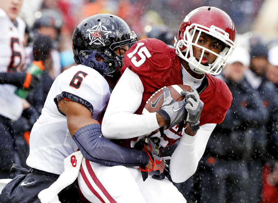 Photo - Oklahoma's Jeffery Mead (15) is tackled by Oklahoma State's Ashton Lampkin (6) after a catch during the Bedlam college football game between the Oklahoma Sooners (OU) and the Oklahoma State Cowboys (OSU) at Gaylord Family - Oklahoma Memorial Stadium in Norman, Okla., Saturday, Dec. 3, 2016. Photo by Steve Sisney, The Oklahoman