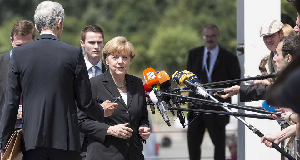 Photo - German Chancellor Angela Merkel, center, speaks with the press as she arrives for an European People's Party meeting in Kortrijk, Belgium on Thursday, June 26, 2014. European Union heads of state will gather on Thursday for the first day of an EU summit in the city Ypres and will participate in a ceremony to commemorate the outbreak of World War I under the Menin Gate.  (AP Photo/Thierry Monasse)