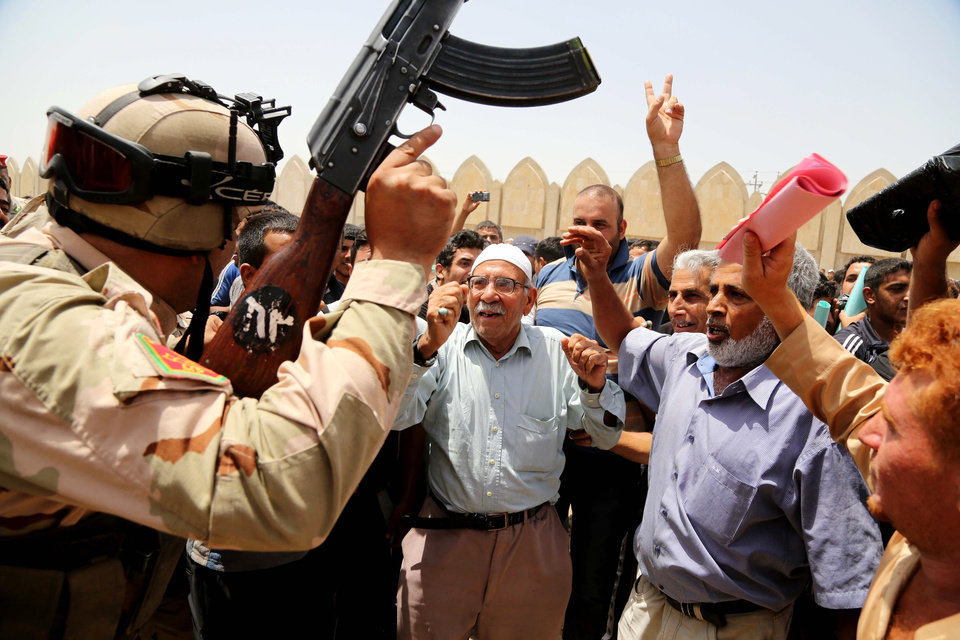 Photo - Iraqi men chant slogans against the al-Qaida breakaway group Islamic State of Iraq and the Levant (ISIL), outside of the main army recruiting center to volunteer for military service in Baghdad, Iraq, Thursday, June. 12, 2014, after authorities urged Iraqis to help battle insurgents.  The al-Qaida-inspired group that led the charge in capturing two key Sunni-dominated cities in Iraq this week vowed on Thursday to march on to Baghdad, raising fears about the Shiite-led government's ability to slow the assault following the insurgents' lightning gains. (AP Photo/ Karim Kadim)