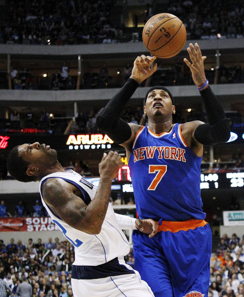 Photo -   Dallas Mavericks' O.J. Mayo (32) is knocked backwards after taking an elbow from New York Knicks' Carmelo Anthony (7) in the first half of an NBA basketball game, Wednesday, Nov. 21, 2012, in Dallas. Anthony was charged with a foul on the play. (AP Photo/Tony Gutierrez)