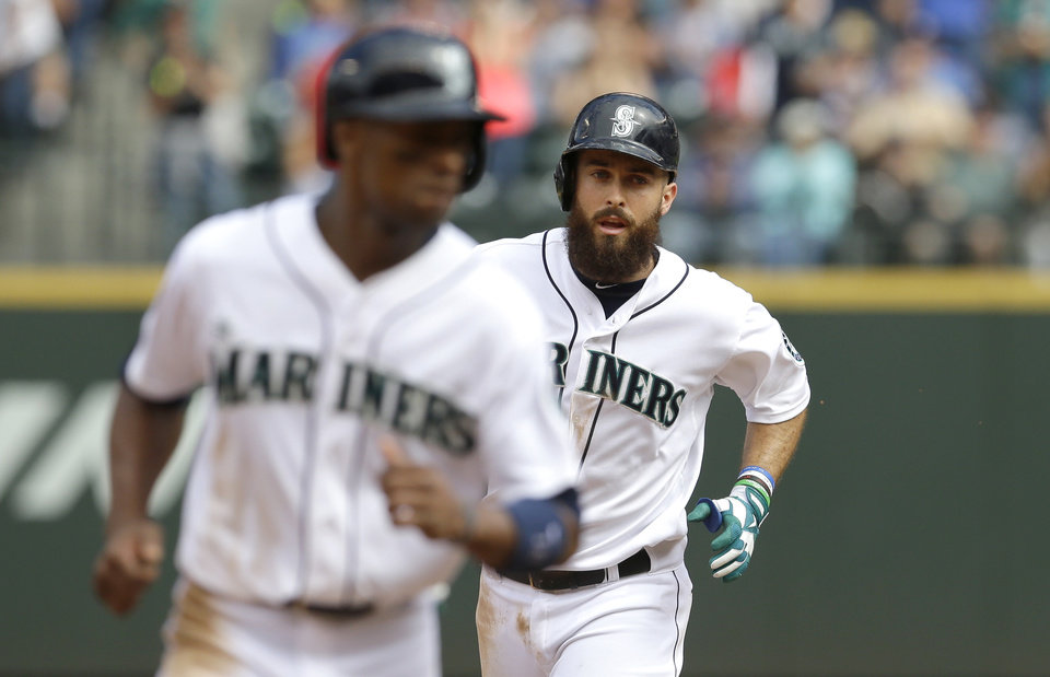 Photo - Seattle Mariners' Dustin Ackley, right, rounds the bases behind  teammate Austin Jackson, left, after hitting a three-run home run in the fifth inning of a baseball game against the Washington Nationals, Sunday, Aug. 31, 2014, in Seattle. (AP Photo/Ted S. Warren)