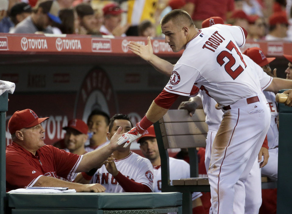 Photo - Los Angeles Angels' Mike Trout is greeted in the dugout after scoring on a hit by Howie Kendrick during the first inning of a baseball game against the Miami Marlins in Anaheim, Calif., Tuesday, Aug. 26, 2014. (AP Photo/Chris Carlson)