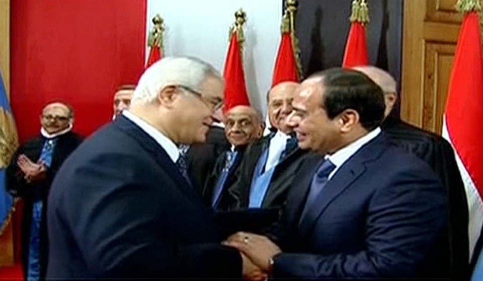Photo - This image made from Egyptian State Television shows newly sworn in President Abdel-Fattah el-Sissi, right, being congratulated by outgoing interim President Adly Mansour, center left, after a ceremony at the Supreme Constitutional Court in Cairo, Egypt, Sunday, June 8, 2014. El-Sissi's inauguration Sunday comes less than a year after the 59-year-old career infantry officer ousted the country's first freely elected president, the Islamist Mohammed Morsi, following days of mass protests by Egyptians demanding he step down. (AP Photo/Egyptian State Television)