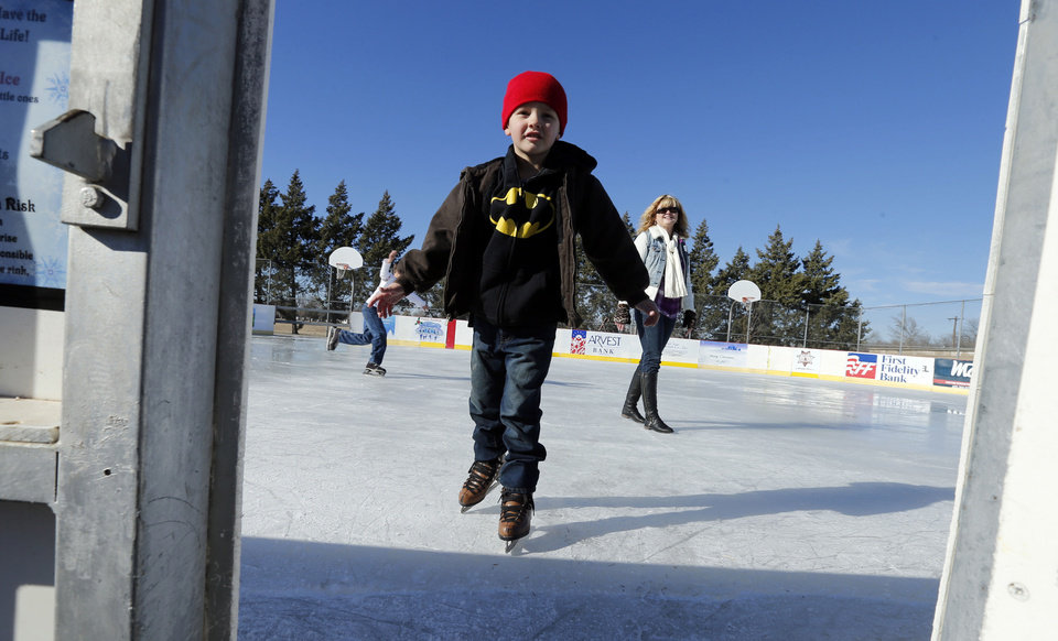 Photo - Weston Setzer, 5, leaves the ice under the watchful eye of his grandmother Rhonda Zimmer as they skate at the outdoor rink at Andrews Park in Norman. PHOTO BY STEVE SISNEY, THE OKLAHOMAN  STEVE SISNEY