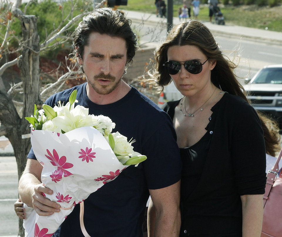 Photo -   Actor Christian Bale and his wife Sibi Blazic carry flowers to place on a memorial to the victims of Friday's mass shooting, Tuesday, July 24, 2012, in Aurora, Colo. Twelve people were killed when a gunman opened fire during a late-night showing of the movie