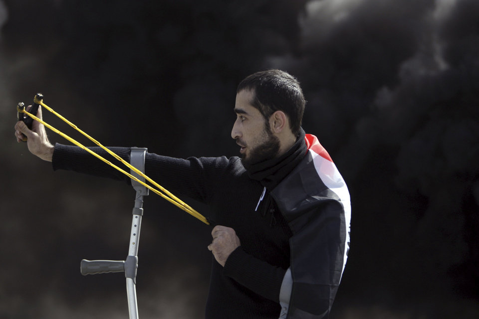 Photo - A Palestinian man aims a sling shot at Israeli soldiers during clashes north of the West Bank city of Jenin after a rally in support of the Palestinian prisoners in Israeli jails, Sunday, Feb. 24, 2013. The death of a 30-year-old Palestinian after interrogation by Israel's Shin Bet security service stokes new West Bank clashes, along with Israeli fears of a third Palestinian uprising. (AP Photo/Mohammed Ballas)
