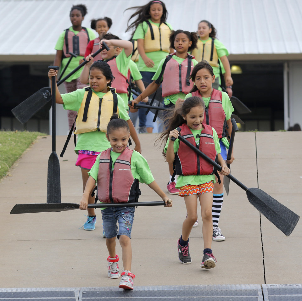 Photo -  Academy students carry their oars to their dragon boat. [Photo By Steve Gooch, The Oklahoman]