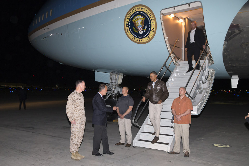 Photo - President Barack Obama is greeted by US Ambassador to Afghanistan James Cunningham, second from left, and Marine General Joseph Dunford, commander of the US-led International Security Assistance Force (ISAF), left, as he steps off Air Force One after arriving at Bagram Air Field for an unannounced visit, on Sunday, May 25, 2014, north of Kabul, Afghanistan. (AP Photo/ Evan Vucci)