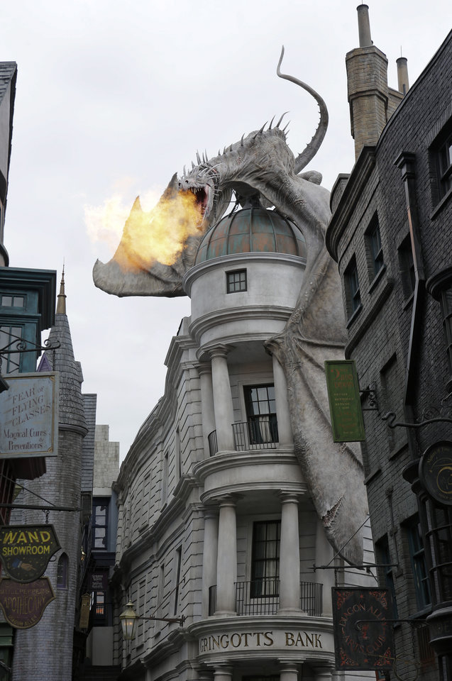 Photo - A dragon breathes fire from atop Gringnotts Bank during a preview of Diagon Alley at the Wizarding World of Harry Potter at Universal Orlando, Thursday, June 19, 2014, in Orlando, Fla. (AP Photo/John Raoux)