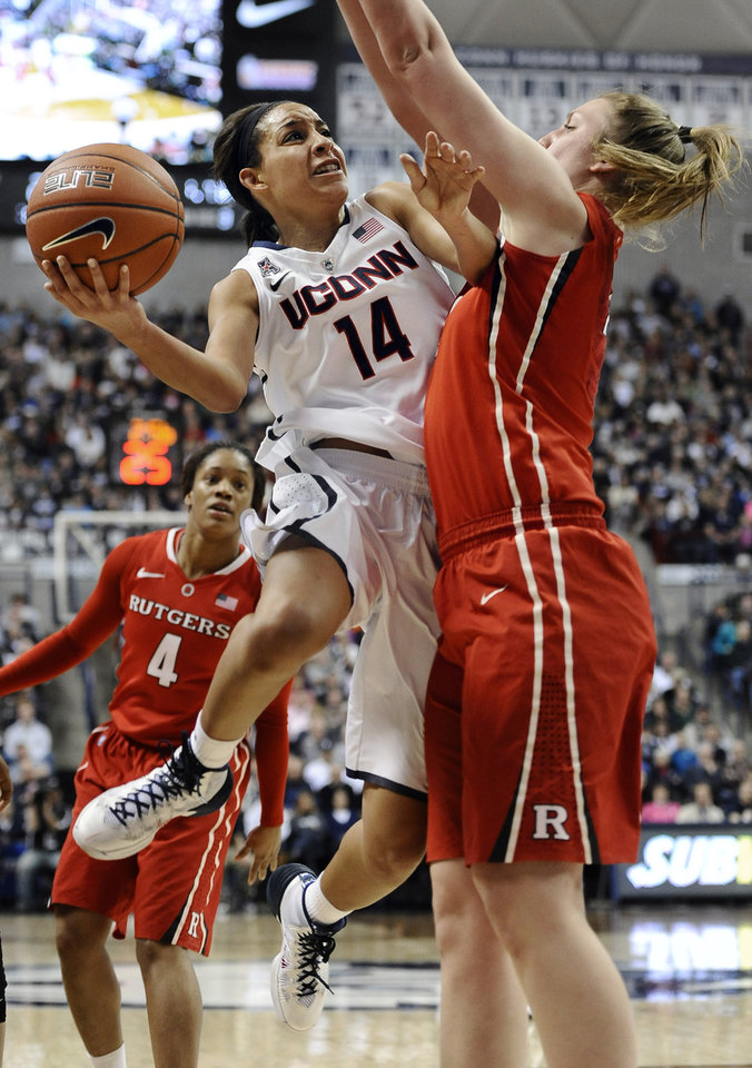 Photo - Connecticut's Bria Hartley drives to the basket and is fouled by Rutgers' Christa Evans, right, during the first half an NCAA college basketball game, Saturday, March 1, 2014, in Storrs, Conn. (AP Photo/Jessica Hill)
