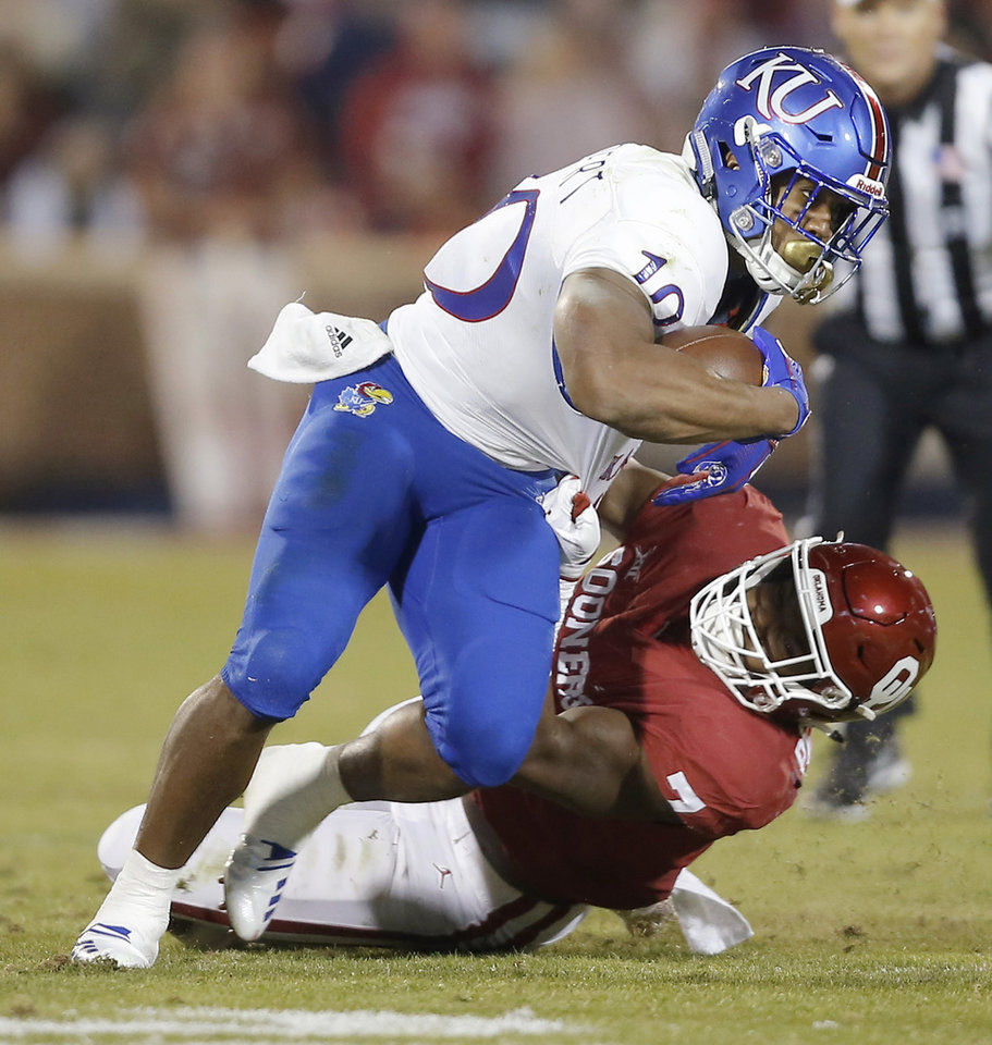 Photo - Oklahoma's Ronnie Perkins (7) brings down Kansas' Khalil Herbert (10) during a college football game between the University of Oklahoma Sooners (OU) and the Kansas Jayhawks (KU) at Gaylord Family-Oklahoma Memorial Stadium in Norman, Okla., Saturday, Nov. 17, 2018. Photo by Bryan Terry, The Oklahoman