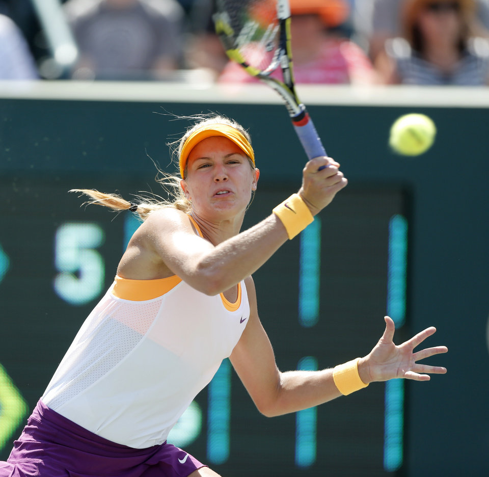 Photo - Eugenie Bouchard, of Canada, returns to Venus Williams during the Family Circle Cup tennis tournament in Charleston, S.C., Thursday, April 3, 2014. (AP Photo/Mic Smith)