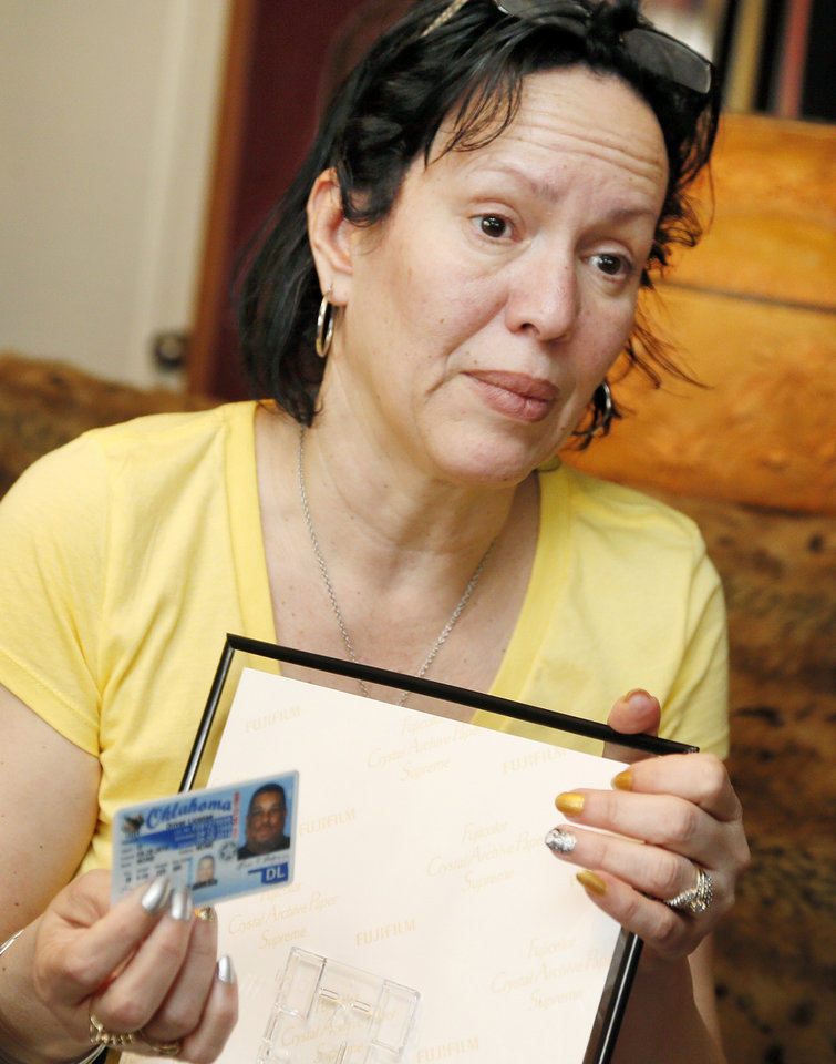 Photo - Nair Rodriguez holds the driver's license of her husband, Luis Rodriguez, at the Rodriguez family's home in Norman. The Moore Police Department is investigating its officers actions leading up to Luis Rodriguez's death outside the Warren Theatre early Saturday.                    Photo by Nate Billings, The Oklahoman