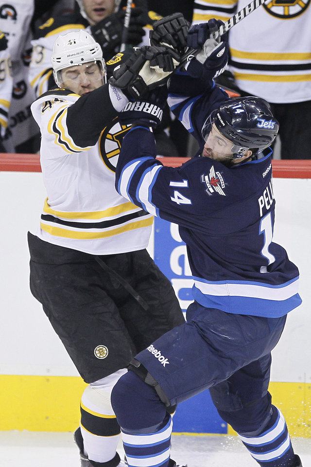 Photo - Boston Bruins' Andrej Meszaros (41) mixes it up with Winnipeg Jets' Anthony Peluso (14) during the first period of an NHL hockey game Thursday, April 10, 2014, in Winnipeg, Manitoba. (AP Photo/The Canadian Press, John Woods)