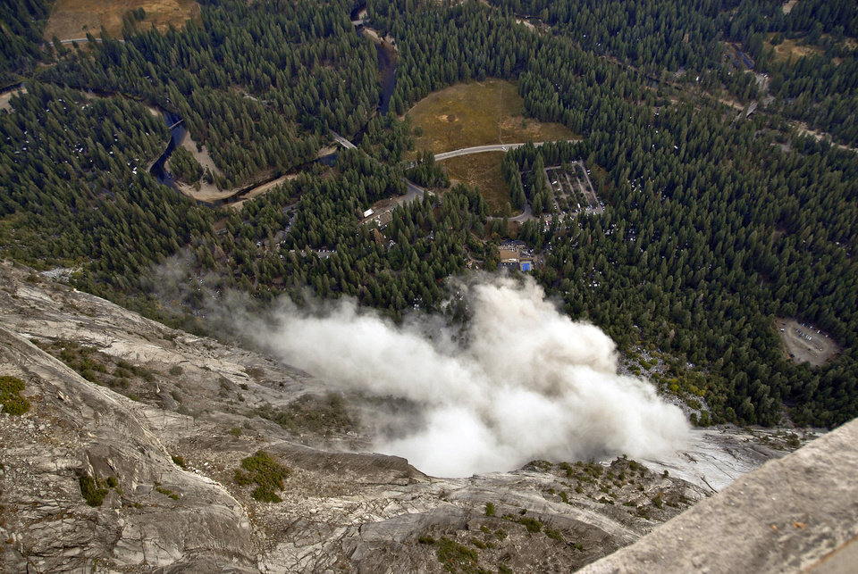Photo -   FILE - In this Oct. 8, 2008, file photo, a dust cloud is seen from the Glacier Point overlook during a rock fall that damaged lodging facilities at Curry Village in Yosemite National Park, Calif. Falling boulders are the single biggest force shaping Yosemite Valley, one of the most popular tourist destinations in the nation's system of national parks. Now large swaths of popular haunts deemed unsafe are closing as officials acknowledge they knew for more than a decade ago that unsuspecting tourists were being lodged in harm's way. On Thursday, June 14, 2012, the National Park Service will announce that potential danger from the unstable 3,000-foot-tall slab of granite known as Glacier Point, a picturesque promontory that for decades has provided a dramatic backdrop to park entertainment events, will leave uninhabitable large parts of Yosemite Valley's most popular lodging areas. (AP Photo/Jim Nichols, File)