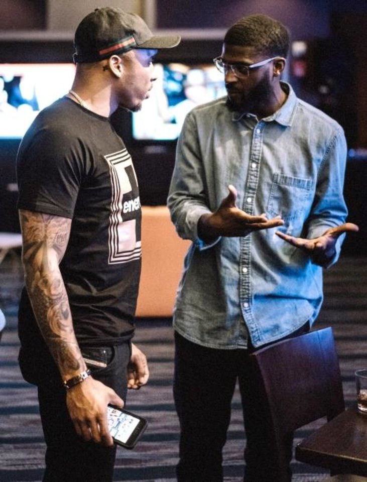 Photo -  Former Oklahoma State defensive back Andrew McGee, right, speaks to Steadman Bailey. The NFL wide receiver is the first client of McGee's new company iinfluence, which is geared toward equipping players to be entrepreneurs and innovators. [PHOTO PROVIDED]