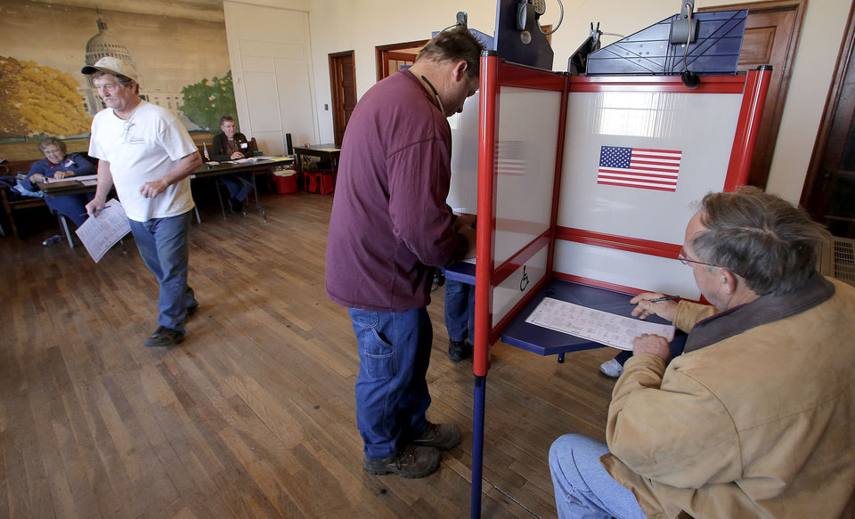 Voters cast their ballots at the old Brown School Tuesday, Nov. 6, 2012, in rural Wellsville, Kan. After a grinding presidential campaign, Americans head into polling places across the country.(AP Photo/Charlie Riedel)