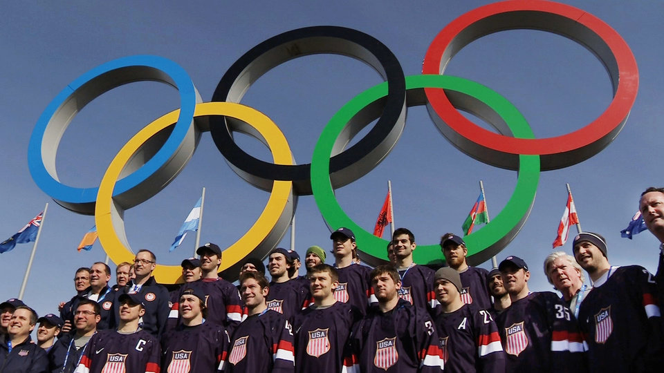 Photo - In this still image taken from video, members of the men's ice hockey team from the United States post in front of the Olympic rings in Olympic Park during the 2014 Winter Olympics in Sochi, Russia, on Thursday, Feb. 20, 2014. The U.S. and Canada will play each other in the semifinal round on Friday, Feb. 21. (AP Photo/Ben Jary)