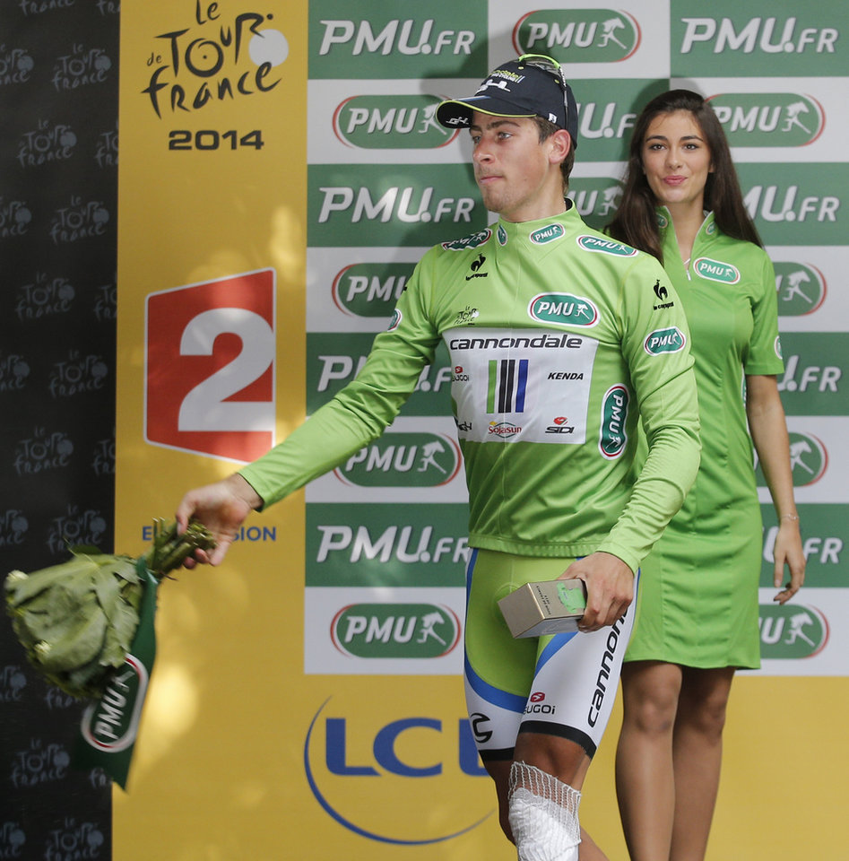Photo - Peter Sagan of Slovakia, wearing the best sprinter's green jersey, thaws his flowers to fans on the podium of the  seventh stage of the Tour de France cycling race over 234.5 kilometers (145.7 miles) with start in Epernay and finish in Nancy, France, Friday, July 11, 2014. (AP Photo/Christophe Ena)