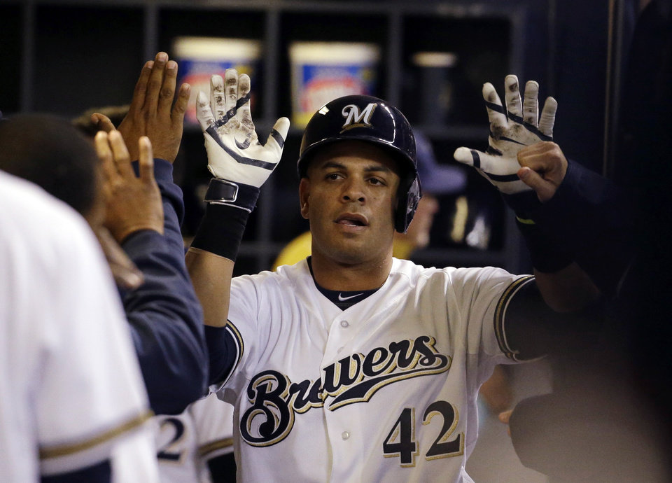 Photo - Milwaukee Brewers' Aramis Ramirez is congratulated in the dugout after hitting a home run during the fifth inning of the MLB National League baseball game against the St. Louis Cardinals Tuesday, April 15, 2014, in Milwaukee. (AP Photo/Morry Gash)