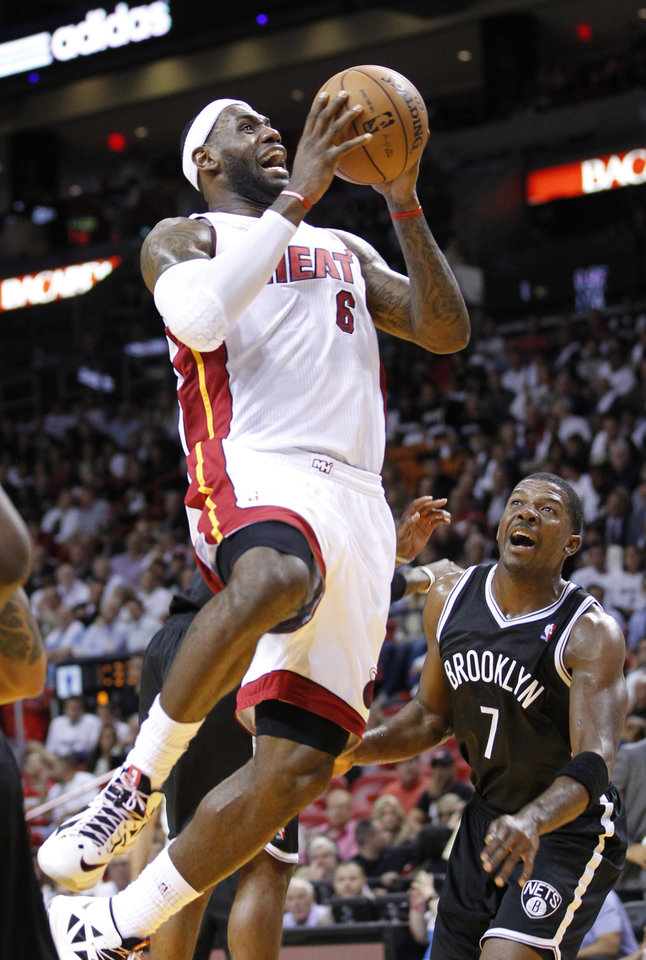 Miami Heat forward LeBron James (6) goes up for a shot against Brooklyn Nets guard Joe Johnson (7) during the first half of an NBA basketball game, Wednesday, Nov. 7, 2012, in Miami. (AP Photo/Wilfredo Lee)