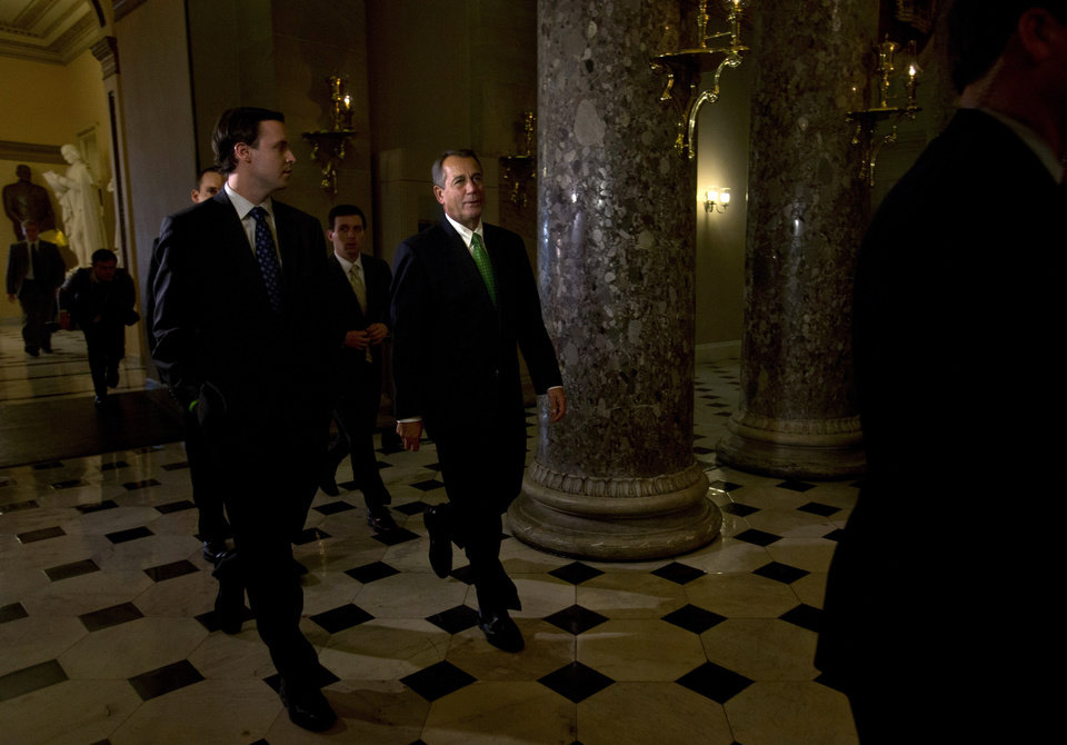 Photo - Speaker of the House John Boehner, R-Ohio, center, returns to his office from the House chamber, as talks continue regarding the
