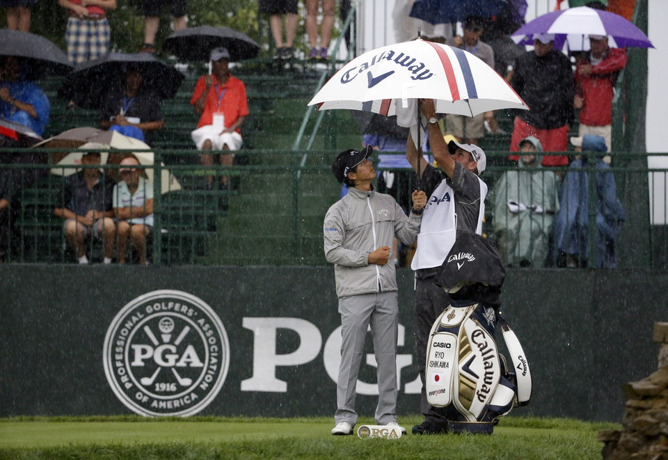 Photo - Ryo Ishikawa, of Japan, puts up an umbrella on the range before the second round of the PGA Championship golf tournament at Valhalla Golf Club on Friday, Aug. 8, 2014, in Louisville, Ky. (AP Photo/David J. Phillip)