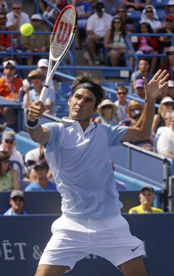 Photo - Roger Federer, from Switzerland, volleys against Tommy Haas, from Germany, at the Western & Southern Open tennis tournament, Thursday, Aug. 15, 2013, in Mason, Ohio. (AP Photo/Al Behrman)