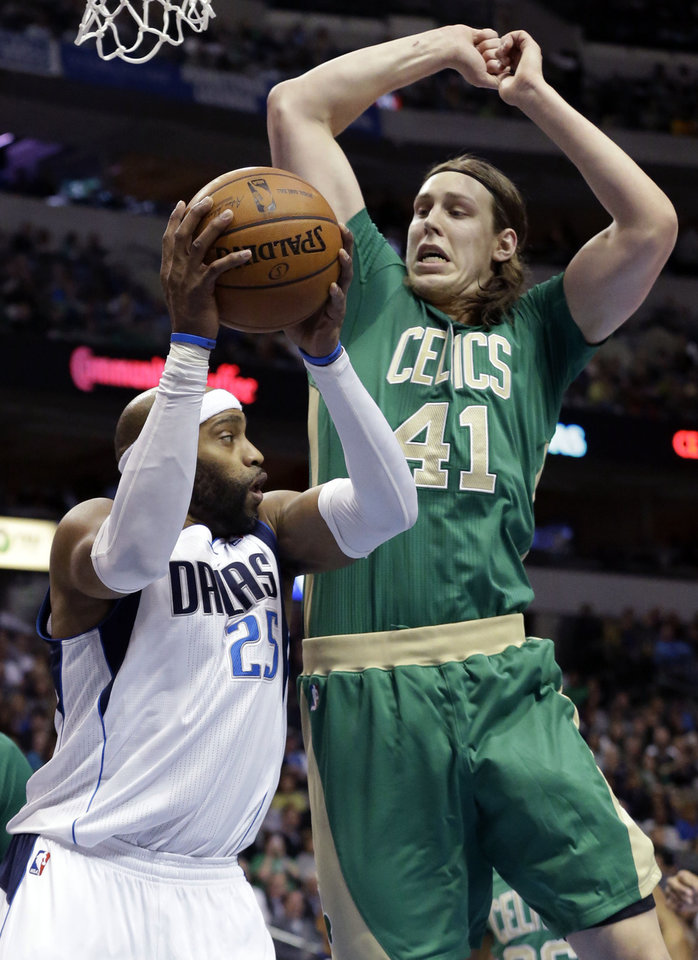 Photo - Dallas Mavericks guard Vince Carter (25) grabs the rebound in front of Boston Celtics center Kelly Olynyk (41) during the first half an NBA basketball game Monday, March 17, 2014, in Dallas. (AP Photo/LM Otero)