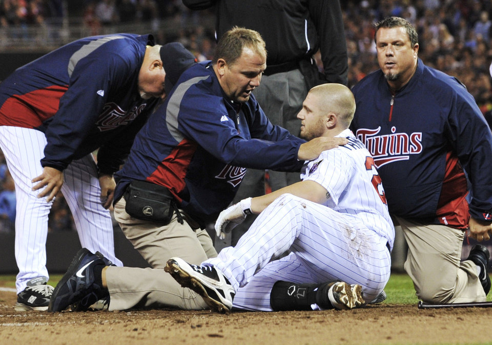 Photo -   Minnesota Twins manager Ron Gardenhire, left, stands by as trainers attend to Chris Parmelee, who was hit in the helmet by a pitch from Boston Red Sox's Justin Thomas in the sixth inning of a baseball game Wednesday, April 25, 2012, in Minneapolis. Parmelee left the game. (AP Photo/Jim Mone)