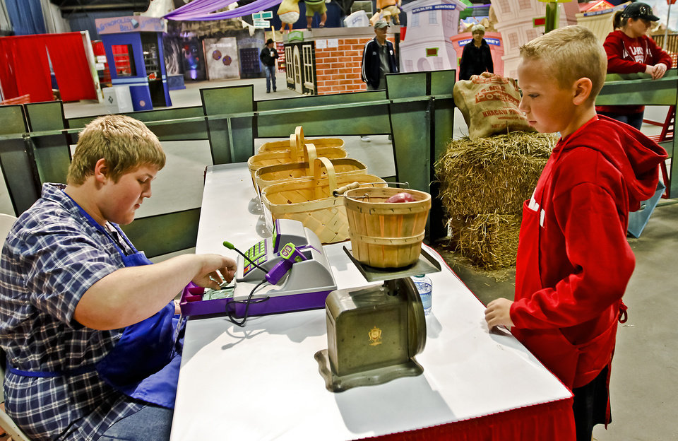 Photo - Carson Biggerstaff, right, takes part in the AGtropolis farmers market with the help of Robert Hofegartner at the Oklahoma State Fair at State Fair Park on Friday, Sept. 14, 2012, in Oklahoma City, Oklahoma.  Photo by Chris Landsberger, The Oklahoman