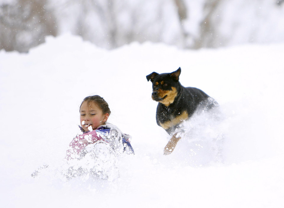 Aliyah Fernandez, 6, leaps into the powder as the family dog Boo Boo runs behind at Washington Park on Wednesday, April 17, 2013, Casper, Wyo. A persistent spring snowstorm socked much of Wyoming for a third straight day Wednesday, closing major interstates and boosting sales of snow removal equipment that had been stowed away for the season. (AP Photo/Dan Cepeda, Casper Star-Tribune)