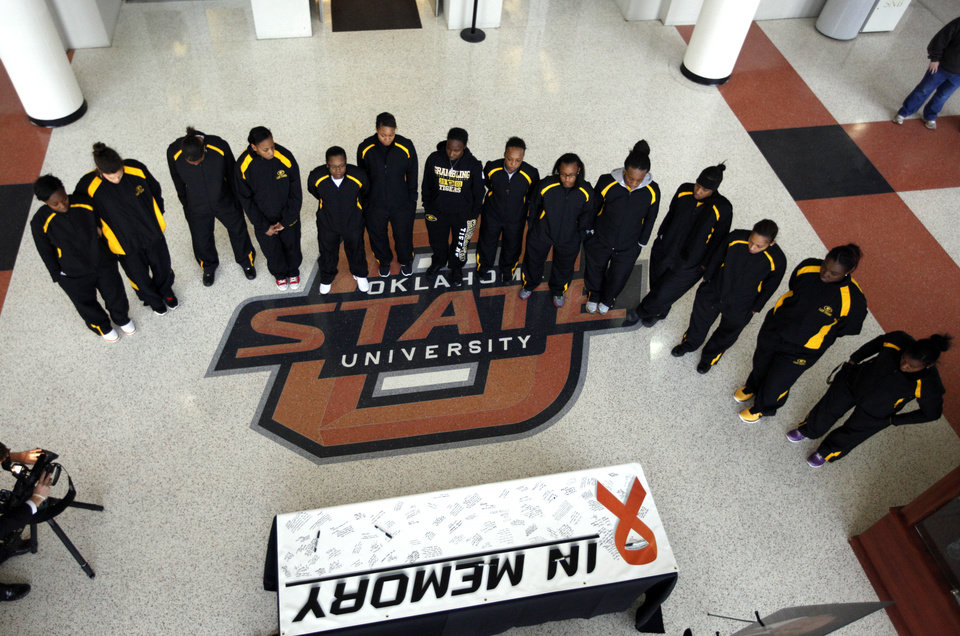 The Grambling Women's basketball team stands at a memorial for  OSU women's head coach Kurt Budke and assistant coach Miranda Serna at Gallagher-Iba Arena in Stillwater, Okla.,  Friday, Nov. 18, 2011.  Photo by Sarah Phipps, The Oklahoman