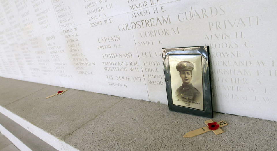 Photo - A wooden cross with a paper poppy and a photo are left as a memento at a war memorial in Arras, France, on Wednesday, April 17, 2013. Commonwealth cemeteries and monuments around the world are currently being renovated in preparation for visitors to centenary events which begin in 2014. (AP Photo/Virginia Mayo)