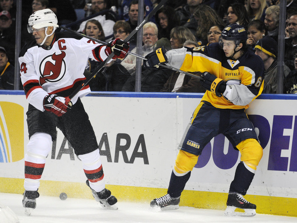 Photo - New Jersey Devils defenseman Bryce Salvador (24) takes a high stick to the helmet from Buffalo Sabres center Brian Flynn (65) as they battle for the puck alongside the net during the first period of an NHL hockey game in Buffalo, N.Y., Saturday, Jan. 4, 2014. (AP Photo/Gary Wiepert)