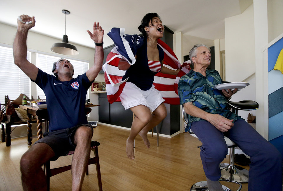 Photo - FILE - In this Sunday, June 22, 2014 file photo, Ed Pollard, left, Tina Termsomket and John Courte react after Portugal scored against USA during the first half while watching a televised group G World Cup soccer match at a watch party in Newport Beach, Calif. The match was almost certainly the most-watched soccer game ever in the U.S., an emphatic confirmation of the sport's rising popularity in a country slower to embrace it than the rest of the world. (AP Photo/Chris Carlson, File)