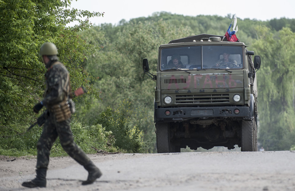 Photo - A truck with Pro-Russian men drives through a street in the town of Lysychansk, Ukraine, Thursday, May 22, 2014. In the eastern Luhansk region, sustained gunfire and shelling rocked the town of Lysychansk. One mortar bomb hit a house, which burst into flames. Earlier today at least 11 Ukrainian troops were killed and about 30 others were wounded during an attack at a military checkpoint, the deadliest raid in the weeks of fighting in eastern Ukraine. (AP Photo/Evgeniy Maloletka)