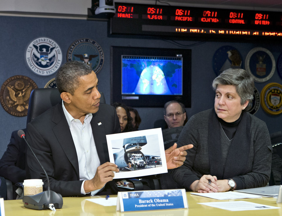Photo -   President Barack Obama visits the Federal Emergency Management Agency (FEMA) for an update on the recovery from Hurricane Sandy that hit New York and New Jersey especially hard as well as much of the East Coast earlier this week, Saturday morning, Nov. 3, 2012, in Washington. He is joined by Homeland Security Secretary Janet Napolitano, right, as he displays a photo of an Air Force C-17 transporting utility trucks to aid the devastated areas. (AP Photo/J. Scott Applewhite)