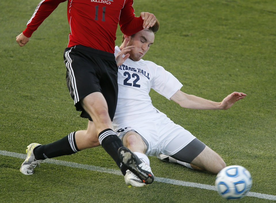 Photo - Heritage Hall's Will Snoddy slides for the ball under Skiatook's Bryce Shook during the Class 5A boys soccer championship between Heritage Hall and Skiatook in Norman, Okla., Friday, May 16, 2014. Photo by Bryan Terry, The Oklahoman
