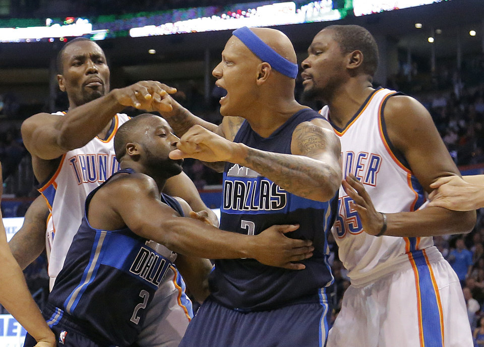 Photo - A scuffle between Oklahoma City's Serge Ibaka (9) and Dallas' Charlie Villanueva (3) is broken up during the NBA basketball game between the Oklahoma City Thunder and the Dallas Mavericks at Chesapeake Energy Arena on Wednesday, Jan. 13, 2016, in Oklahoma City, Okla.  Dallas' Charlie Villanueva (3) was ejected from the game after receiving a double technical foul. Photo by Chris Landsberger, The Oklahoman