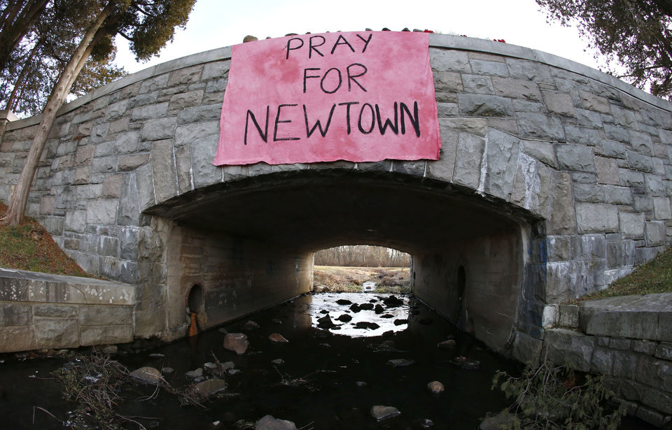 Photo - In this photo taken with a fisheye lens, a message honoring the victims that died a day earlier when a gunman opened fire at an elementary hang from a bridge near Hawley Pond, Saturday, Dec. 15, 2012, in Newtown, Conn. The massacre of 26 children and adults at Sandy Hook Elementary school elicited horror and soul-searching around the world even as it raised more basic questions about why the gunman, 20-year-old Adam Lanza, would have been driven to such a crime and how he chose his victims. (AP Photo/Julio Cortez) ORG XMIT: CTJC128