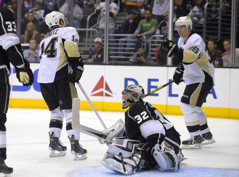 Photo - Pittsburgh Penguins left wing Chris Kunitz, left, celebrates his goal with left wing Jussi Jokinen, of Finland, as Los Angeles Kings goalie Jonathan Quick sits on the ice during the first period of an NHL hockey game, Thursday, Jan. 30, 2014, in Los Angeles. (AP Photo)