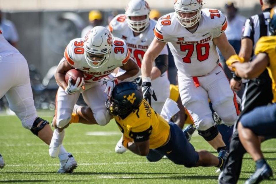 Photo -  Oklahoma State's Chuba Hubbard (30) is tackled by West Virginia's Josh Chandler-Semedo (7) during the first half Saturday. Hubbard ran for 101 yards on 22 carries. [Rob Ferguson/USA TODAY Sports]