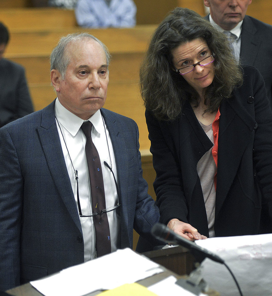 Photo - Singer Paul Simon, left, holds hands with his wife Edie Brickell at a hearing in Norwalk Superior Court on Monday April 28, 2014 in Norwalk, Conn. The couple were arrested Saturday on disorderly conduct charges by officers investigating a family dispute at their home in New Canaan, Conn. (AP Photo/The Hour, Alex von Kleydorff, Pool)
