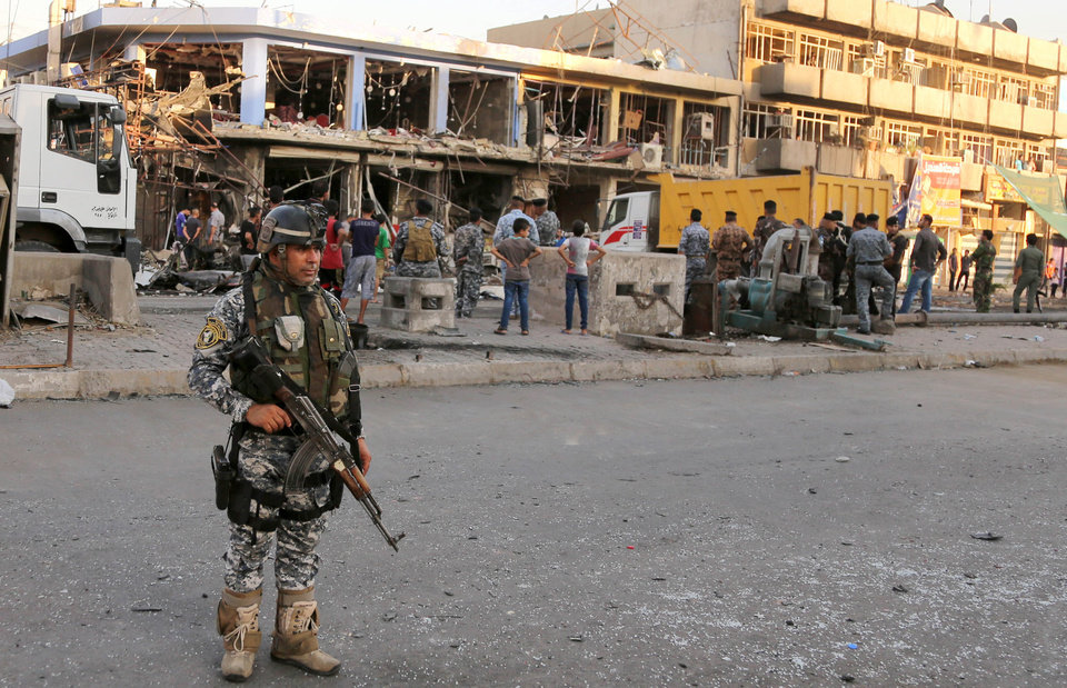 Photo - Iraqi policemen and civilians inspect the site of a car bomb attack near a restaurant in the southeastern district of New Baghdad, Iraq, Wednesday, Aug. 13, 2014. A string of attacks in and around the capital killed more than a dozen and wounded dozens. (AP Photo/Karim Kadim)