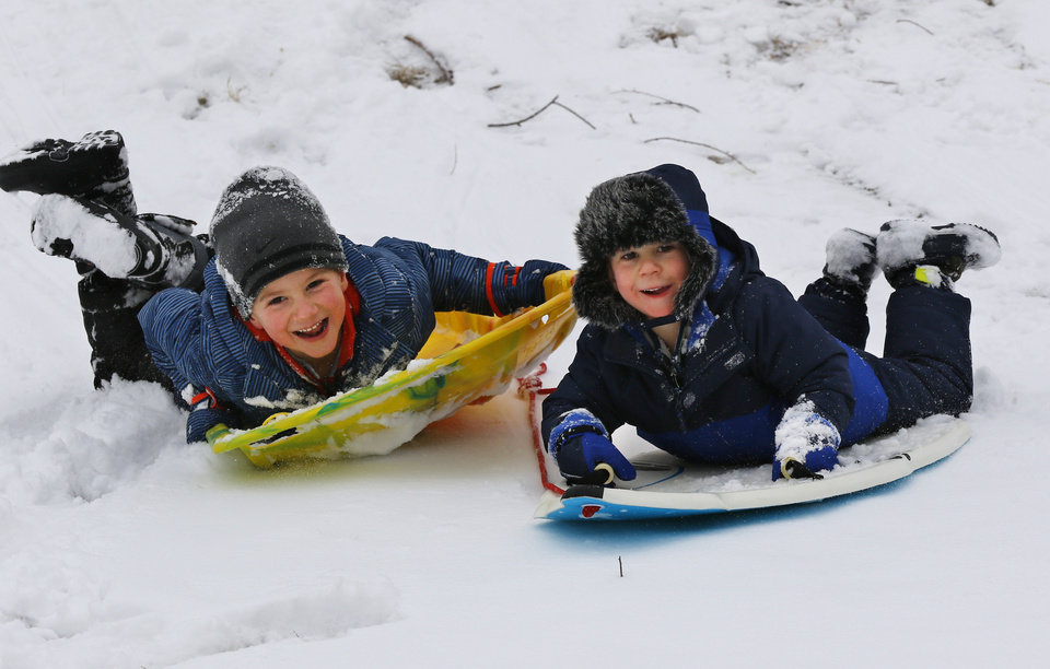 Photo - Bennett and his brother, Owen, sled down a hill while at the park with their grandmother, Jeanne Hapton, at Bickham Rudkin Park in Edmond, Wednesday, February 5, 2020.  [Photo by Doug Hoke/The Oklahoman]