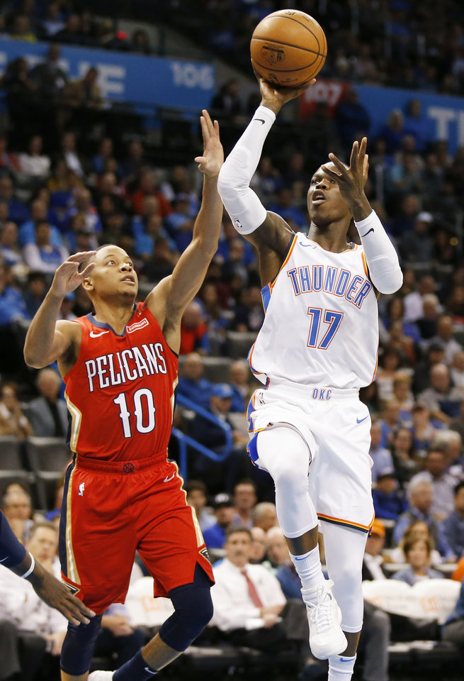 Photo - Oklahoma City's Dennis Schroder (17) shoots next to New Orleans' Tim Frazier (10) during an NBA basketball game between the Oklahoma City Thunder and the New Orleans Pelicans at Chesapeake Energy Arena in Oklahoma City, Monday, Nov. 5, 2018. Photo by Nate Billings, The Oklahoman
