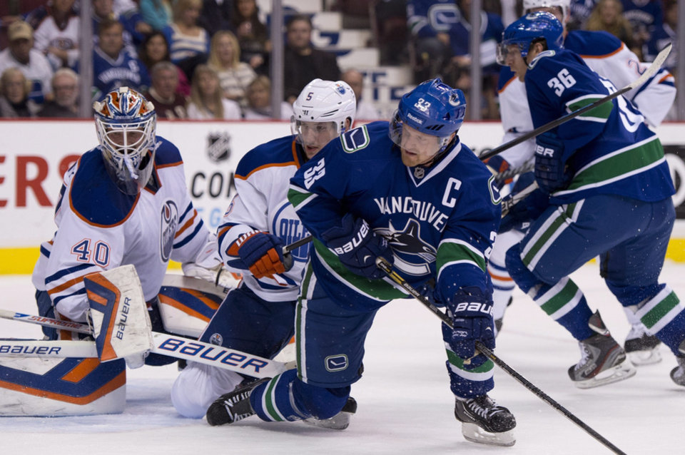 Photo - Vancouver Canucks center Henrik Sedin (33) tries to get a shot past Edmonton Oilers goalie Devan Dubnyk (40) and defenseman Ladislav Smid (5) during the first period of an NHL hockey game in Vancouver, British Columbia, Saturday, Oct. 5, 2013. (AP Photo/The Canadian Press, Jonathan Hayward)