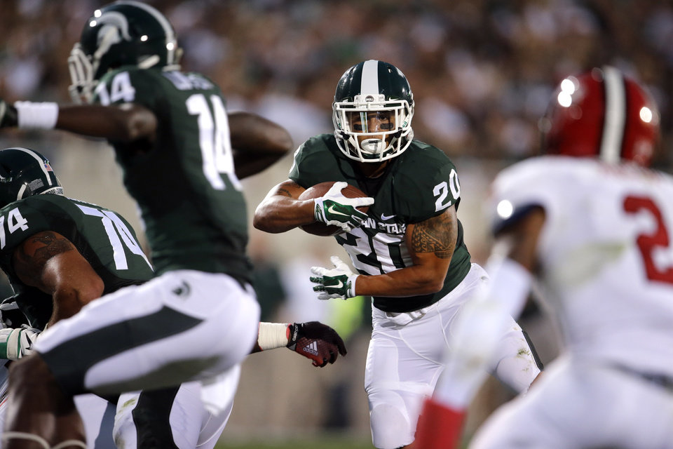 Photo - FILE - In this Aug. 29, 2014, file photo, Michigan State running back Nick Hill (20) looks for running room on a 17-yard touchdown run against the Jacksonville State during the first half of an NCAA college football game in East Lansing, Mich. When No. 7 Michigan State plays at No. 3 Oregon on Saturday, the team with the old-school offense will be the unusual one. While it's become more difficult to categorize offenses these days as philosophies and schemes are blended and combined, the Spartans are among a dwindling number of teams still using what can best be described as a traditional, prostyle attack, featuring tight ends, fullbacks and the quarterback regularly taking a snap from under center. (AP Photo/Paul Sancya, File)